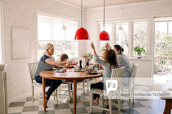 Mütter frühstücken mit ihren Töchtern  während sie im Haus am Esstisch sitzen
