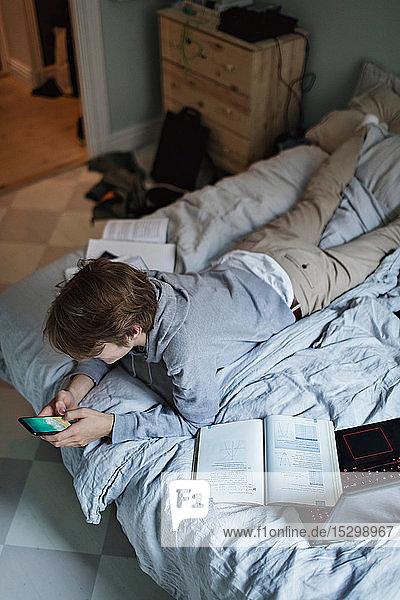 Schrägansicht eines sozialmediensüchtigen Teenagers  der ein Mobiltelefon benutzt  während er im Schlafzimmer neben einem Buch liegt Schrägansicht eines sozialmediensüchtigen Teenagers, der ein Mobiltelefon benutzt, während er im Schlafzimmer neben einem Buch liegt
