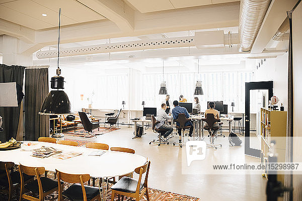 Software-Ingenieure diskutieren am Schreibtisch gegen Fenster im Kreativbüro
