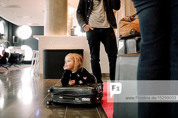 Nachdenkliches Mädchen mit Hand am Kinn  das sich im Hotel an einen Koffer lehnt Nachdenkliches Mädchen mit Hand am Kinn, das sich im Hotel an einen Koffer lehnt