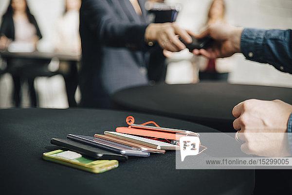 Mittelsektion einer Geschäftsfrau  die einem Geschäftsmann während einer Besprechung im Büro ein Mobiltelefon gibt Mittelsektion einer Geschäftsfrau, die einem Geschäftsmann während einer Besprechung im Büro ein Mobiltelefon gibt