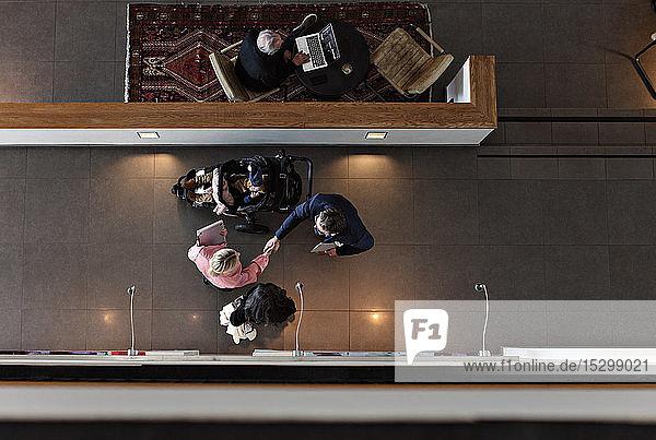 Schrägaufnahme einer Geschäftsfrau  die einem männlichen Kollegen mit Sohn die Hand schüttelt  während sie im Bürokorridor steht