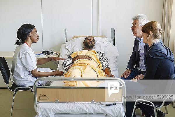 Junger Mann sieht Familie an  während der Arzt auf der Krankenhausstation diskutiert