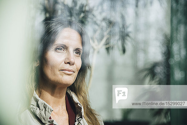 Nachdenkliche reife Geschäftsfrau schaut durch das Fenster im Büro Nachdenkliche reife Geschäftsfrau schaut durch das Fenster im Büro