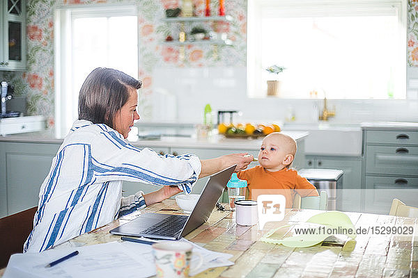 Multi-tasking female freelancer feeding food to daughter while telecommuting at dining table