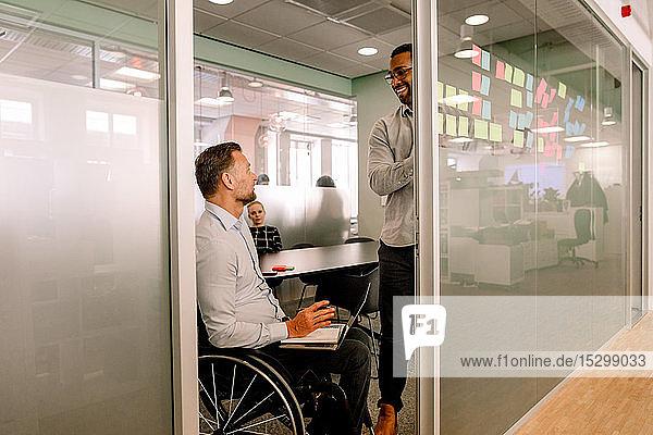 Sales executives having meeting in board room seen through doorway