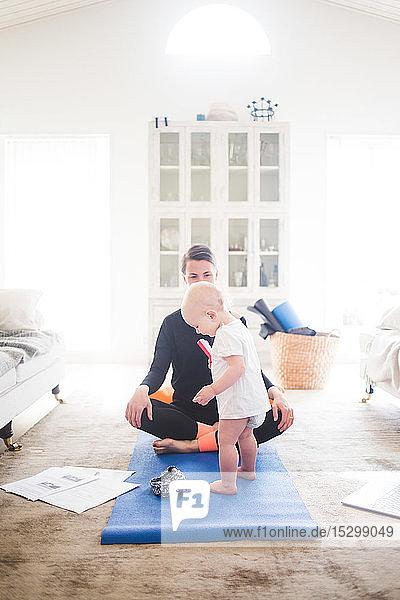 Berufstätige Mutter praktiziert Yoga  während die Tochter zu Hause auf einer Übungsmatte steht
