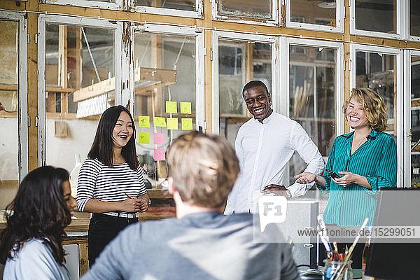 Lächelnde Unternehmer  die im Start-up-Büro an neuen IT-Projekten arbeiten