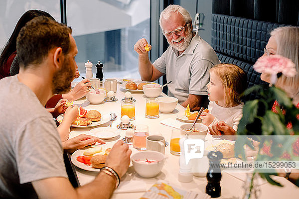 High angle view of multi-generation family having food at table in restaurant