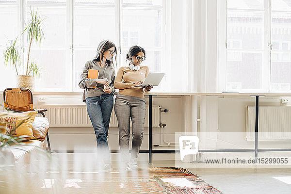 Programmiererinnen  die einen Laptop benutzen  während sie im Büro am Fenster stehen