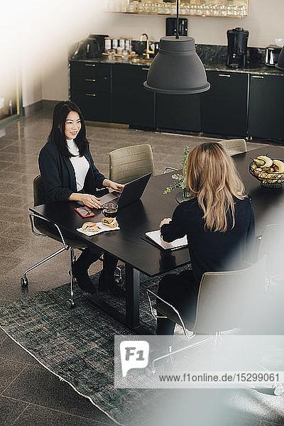 Hochwinkelansicht von weiblichen Fachleuten  die am Konferenztisch zusammenarbeiten Hochwinkelansicht von weiblichen Fachleuten, die am Konferenztisch zusammenarbeiten