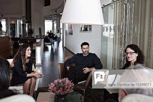 Geschäftsleute diskutieren auf Sesseln sitzend in der Büro-Lobby