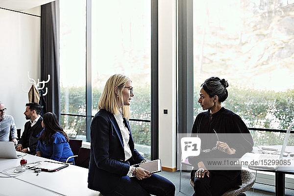 Geschäftsfrauen diskutieren im Sitzungssaal mit Kollegen  die im Hintergrund arbeiten
