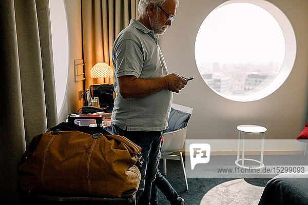 Senior man using smart phone while standing against window in hotel room