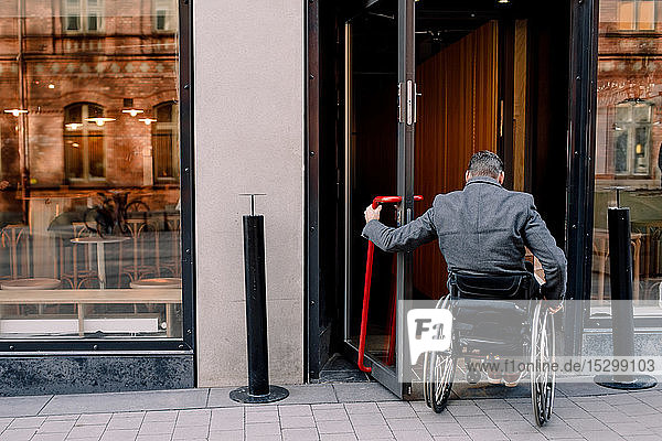 Rückansicht eines behinderten reifen Mannes  der beim Betreten des Ladens auf einem Rollstuhl sitzt