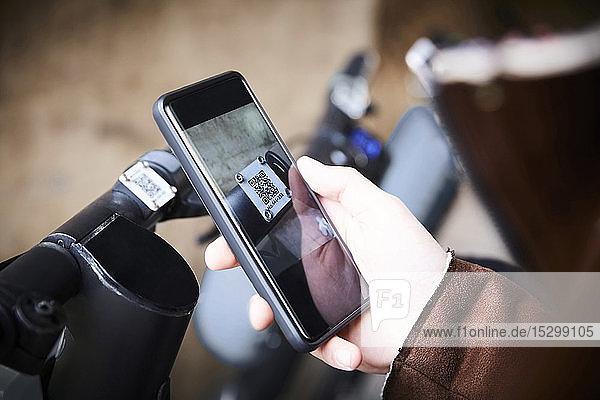 Ausgeschnittenes Bild eines Teenagers  der ein Mobiltelefon über einen elektrischen Roller benutzt