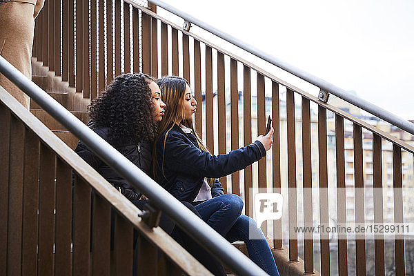 Teenager-Mädchen,  das mit einer Freundin auf der Treppe sitzend Selbstgespräche führt