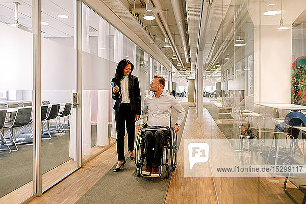 Smiling businesswoman looking at disabled colleague sitting on wheelchair in corridor at work place