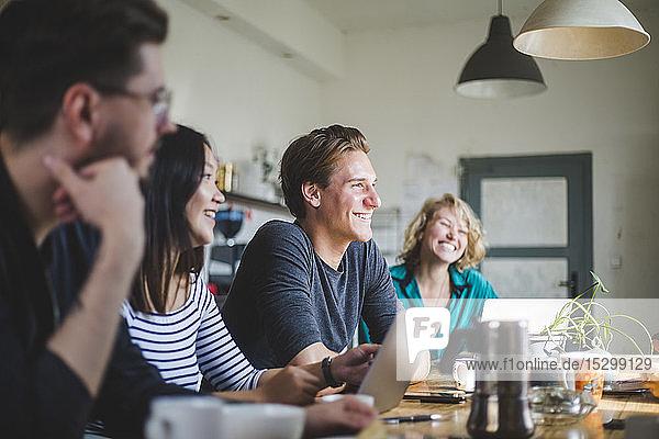 Glückliche Computerprogrammierer  die bei der Arbeit am Tisch im Büro wegschauen