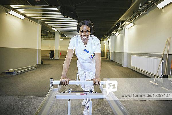 Lächelnde Ärztin mit Krankenhausbahre im beleuchteten Korridor