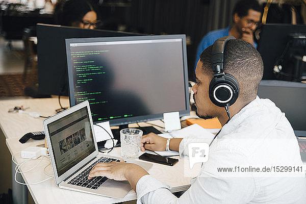 Seitenansicht eines männlichen Programmierers mit Kopfhörer-Codierung über Laptop auf dem Schreibtisch  während er im Büro sitzt