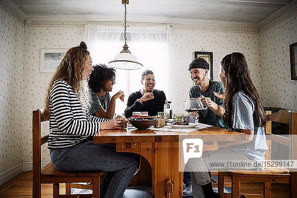 Glückliche Freunde unterhalten sich  während sie zu Hause Essen und Trinken auf dem Tisch genießen