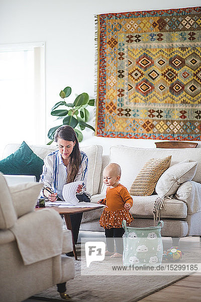 Female professional freelancing while daughter looking at papers on table in living room