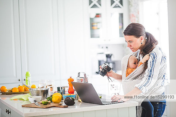 Seitenansicht des Bloggens einer berufstätigen Mutter,  die während des Stillens ihrer Tochter in einem Tragesitz in der Küche Nahrung zu sich nimmt