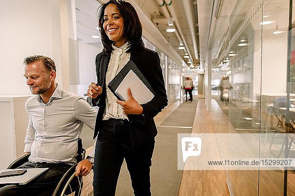 Lächelnde Geschäftsfrau mit behindertem männlichen Manager im Bürokorridor