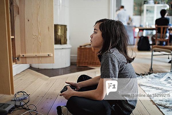 Seitenansicht eines Jungen  der beim Spielen eines Videospiels auf einem Holzboden zu Hause wegschaut