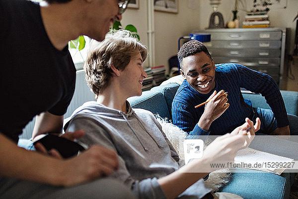 Lächelnder Teenager zeigt Freunden sein Handy auf dem Sofa  während er zu Hause lernt