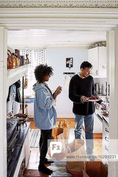 Young woman talking with male friend holding strawberries in plate while standing at home seen through doorway