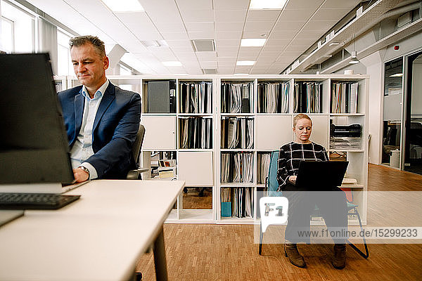 Mature businessman working at desk while businesswoman using laptop in office