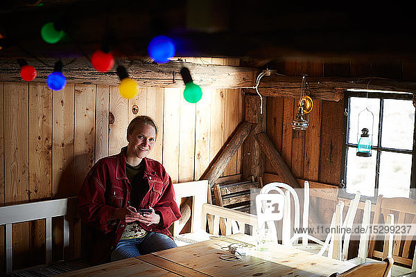Portrait of smiling young woman using smart phone while sitting at table in log cabin