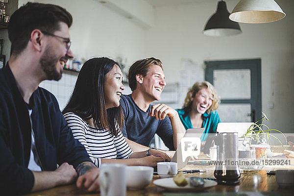 Team professioneller Computerhacker lacht  während sie im Büro am Schreibtisch sitzen