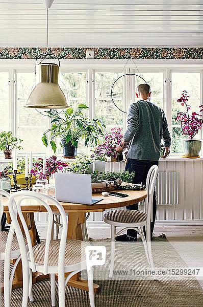 Rückansicht in voller Länge eines Mannes bei der Gartenarbeit im heimischen Zimmer