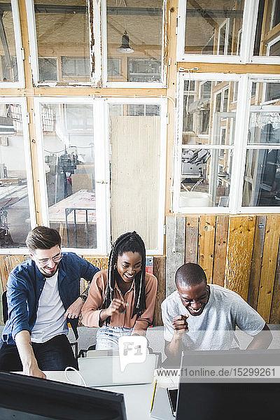 Hochwinkelansicht von lächelnden Computerprogrammierern  die zusammen kodieren  während sie im Büro sitzen