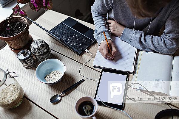 Hochwinkelansicht eines Teenagers  der auf ein Buch schreibt  während er ein digitales Tablett für Hausaufgaben benutzt Hochwinkelansicht eines Teenagers, der auf ein Buch schreibt, während er ein digitales Tablett für Hausaufgaben benutzt
