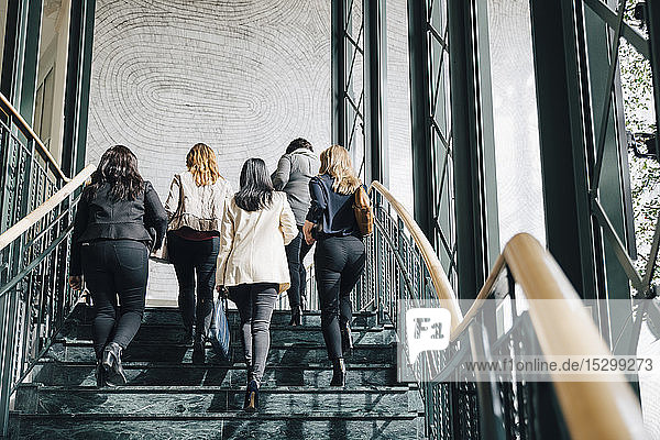 Low angle view of multi-ethnic female entrepreneurs moving up on staircase in office