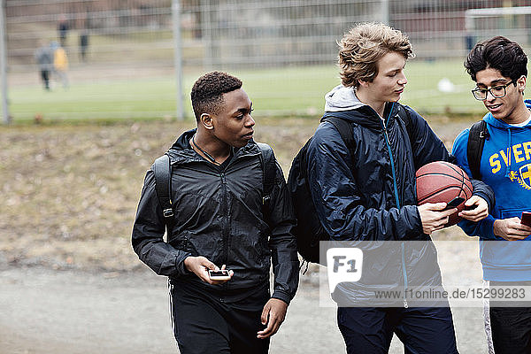 Multi-ethnic friends talking while holding mobile phones on street against playing field