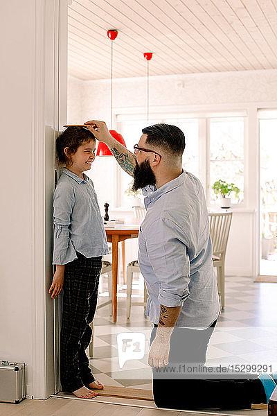 Vater misst zu Hause die Höhe der Tochter an der Wand
