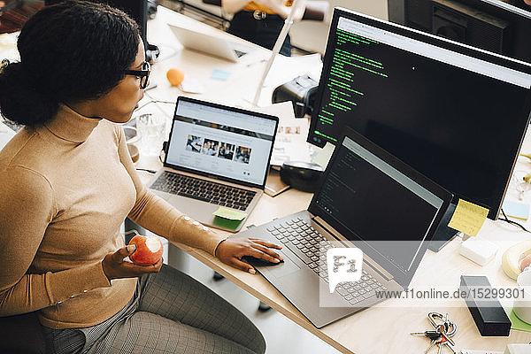 Hochwinkelansicht einer IT-Fachfrau  die einen Apfel hält  während sie einen Laptop auf dem Schreibtisch im Kreativbüro benutzt Hochwinkelansicht einer IT-Fachfrau, die einen Apfel hält, während sie einen Laptop auf dem Schreibtisch im Kreativbüro benutzt