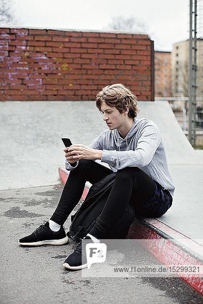 Ein Teenager in voller Länge benutzt ein Smartphone  während er in der Stadt auf der Straße sitzt Ein Teenager in voller Länge benutzt ein Smartphone, während er in der Stadt auf der Straße sitzt