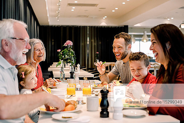 Cheerful family talking while having food at table in restaurant