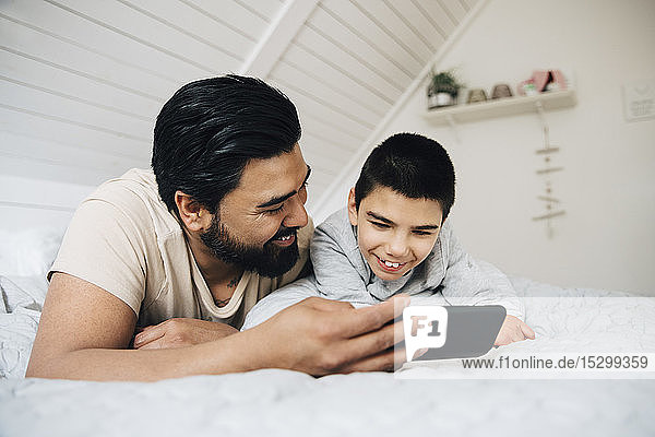 Father and smiling disabled son watching movie over mobile phone while lying on bed at home