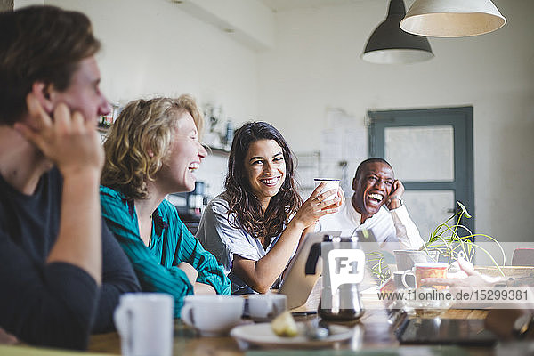 Portrait of cheerful young female computer programmer sitting with hackers at table in creative office