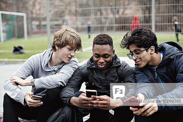 Lächelnde Freunde  die auf das Telefon eines Teenagers schauen  während sie am Fußballfeld sitzen Lächelnde Freunde, die auf das Telefon eines Teenagers schauen, während sie am Fußballfeld sitzen