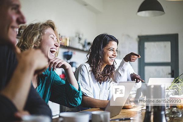Zuversichtlich fröhliche IT-Fachleute sitzen am Tisch  während sie im Kreativbüro arbeiten
