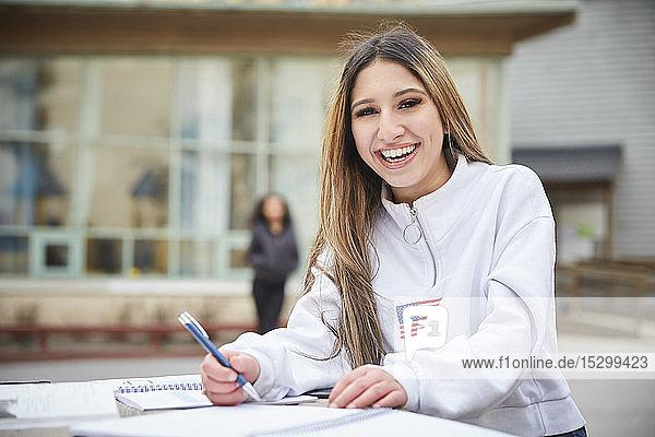 Porträt eines lächelnden Teenager-Mädchens am Tisch auf dem Schulhof Porträt eines lächelnden Teenager-Mädchens am Tisch auf dem Schulhof