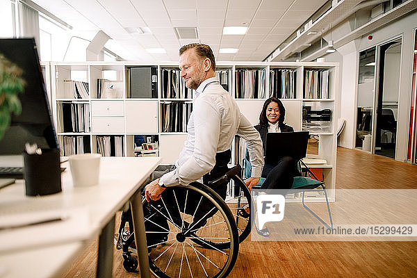Disabled male professional sitting on wheelchair while smiling businesswoman using laptop at work place